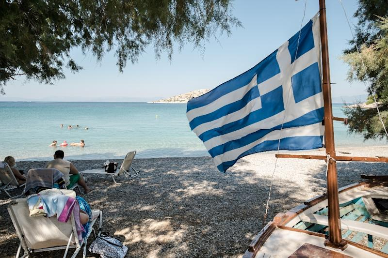 People enjoy the beach on Salamina island near Athens, on July 12, 2015 as eurozone and Greek leaders finally reached a unanimous deal on a third bailout (AFP Photo/Andreas Solaro)