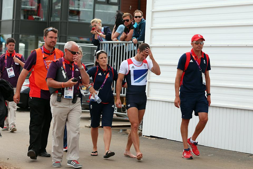WINDSOR, ENGLAND - AUGUST 02: (C) Rower Chris Bartley of Great Britain is helped to the medal stand after having to be pulled out of his boat after winning the silver medal in the Lightweight Men's Four final on Day 6 of the London 2012 Olympic Games at Eton Dorney on August 2, 2012 in Windsor, England. (Photo by Ezra Shaw/Getty Images)