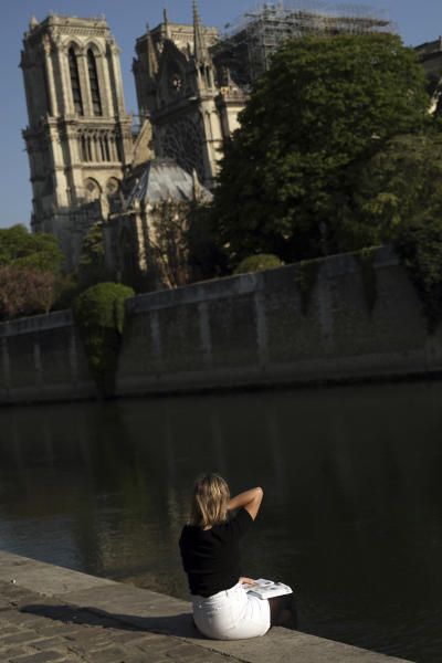 A woman sits by the Seine River near the Notre Dame Cathedral in Paris, Saturday, April 20, 2019. Rebuilding Notre Dame, the 800-year-old Paris cathedral devastated by fire this week, will cost billions of dollars as architects, historians and artisans work to preserve the medieval landmark. (AP Photo/Francisco Seco)