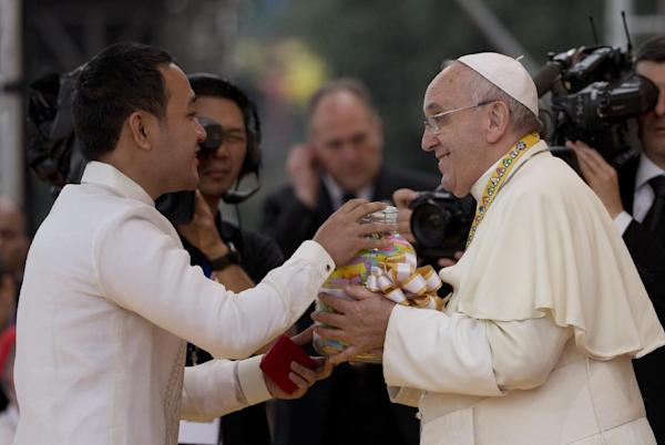Pope Francis is presented with a jar containing message of former street children during his meeting with the youth in Santo Tomas University in Manila, Philippines, Sunday, Jan. 18, 2015. Francis opened his meeting with the Filipino youth on a somber note, reporting to thousands gathered at the centuries-old university the sad news that a female church volunteer had died during his visit to central Tacloban city the previous day, and led prayers for the woman. (AP Photo/Alessandra Tarantino)
