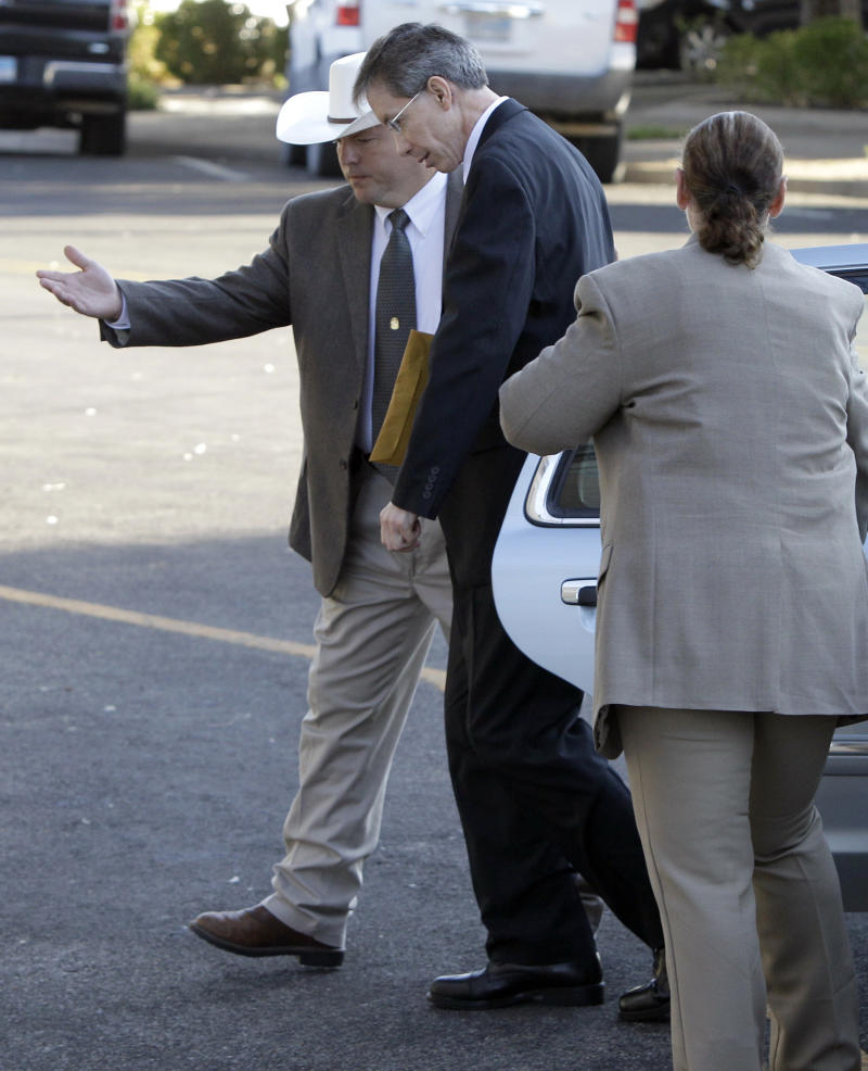 """Law enforcement officials, left, and right, help polygamist religious leader Warren Jeffs out of a vehicle as he arrives at the Tom Green County Courthouse Thursday Aug. 4, 2011, in San Angelo, Texas.  Jeffs, 55, is  accused of sexually assaulting two girls he took as brides during so-called """"spiritual marriages.""""   (AP Photo/Tony Gutierrez)"""
