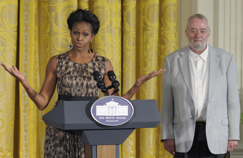 FILE - In this Tuesday, Sept. 13, 2011 file photo, Bill Moggridge, the director of the Smithsonian's Cooper-Hewitt, National Design Museum, stands at right as first lady Michelle Obama speaks in the East Room of the White House in Washington during the Smithsonian's Cooper Hewitt National Design Awards luncheon. Moggridge, a British industrial designer who designed an early portable computer with the flip-open shape that is common today, has died. He was 69. The museum said Moggridge, its director since 2010, died on Saturday, Sept. 8, 2012 after a battle with cancer. (AP Photo/Susan Walsh)