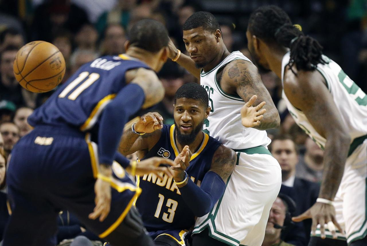 Indiana Pacers' Paul George (13) passes the ball away from Boston Celtics' Marcus Smart, center right, during the first quarter of an NBA basketball game in Boston, Wednesday, March 22, 2017. The Celtics won 109-100. (AP Photo/Michael Dwyer)
