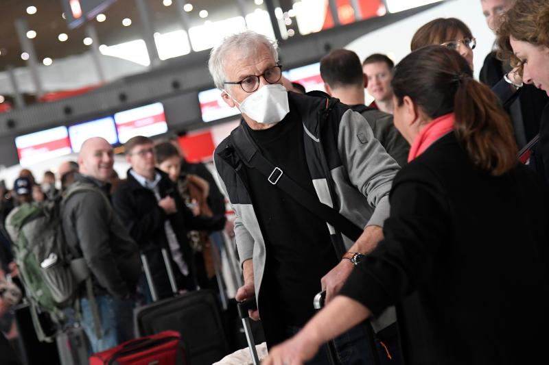 Travellers with protective face masks wait in a check-in line at Paris-Charles-de-Gaulle airport after a US 30-day ban on travel from Europe due to the COVID-19 spread in Roissy-en-France on March 12, 2020. - US President Donald Trump announced on March 11, 2020 a shock 30-day ban on travel from mainland Europe over the coronavirus pandemic that has sparked unprecedented lockdowns, widespread panic and another financial market meltdown. (Photo by Bertrand GUAY / AFP) (Photo by BERTRAND GUAY/AFP via Getty Images)