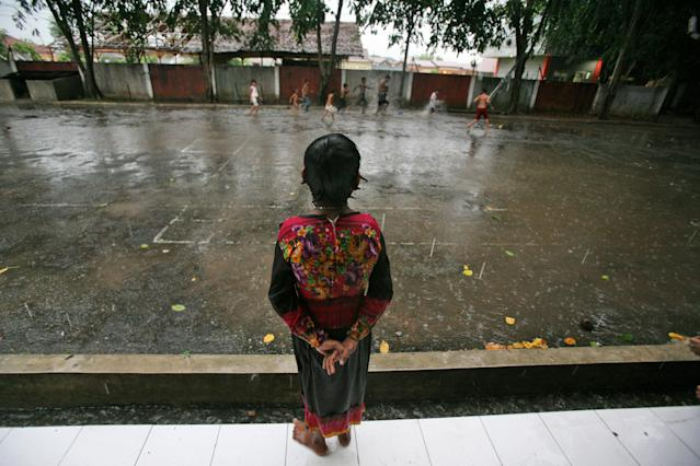 In this Aug. 7, 2013 photo, Senwara Begum, a young ethnic Rohingya asylum seeker, watches her friends play in the rain outside their temporary shelter in Medan, North Sumatra, Indonesia. After her tiny Muslim village in Myanmar's northwest Rakhine had been destroyed in a fire set by an angry Buddhist mob, she and her brother became separated from their family. (AP Photo/Binsar Bakkara)