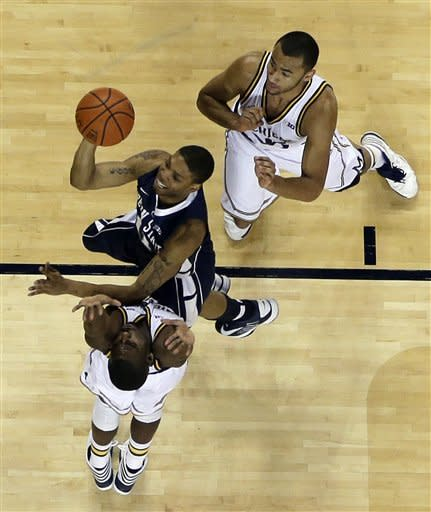 Penn State guard Jermaine Marshall, cenetr, shoots over the defense of Michigan guard Tim Hardaway Jr., bottom, and forward Jon Horford, top, during the second half of an NCAA college basketball game at Crisler Center in Ann Arbor, Mich., Sunday, Feb. 17, 2013. (AP Photo/Carlos Osorio)