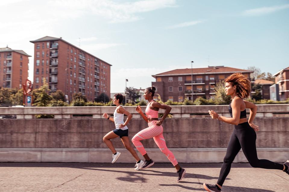 Side view of a three young athletes running on a concrete path in the city