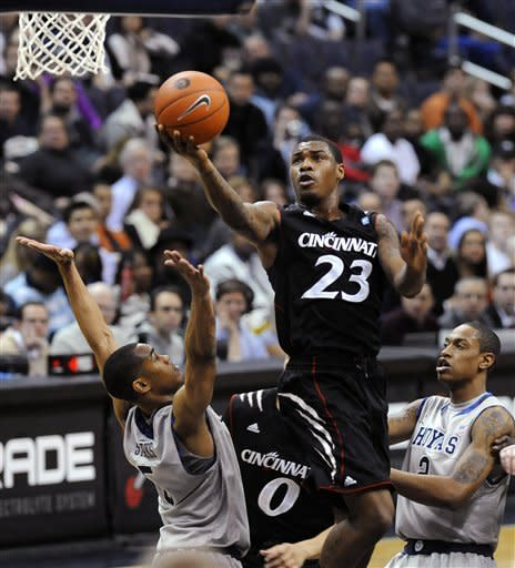 Cincinnati's Sean Kilpatrick (23) splits the defense of Georgetown's Markel Starks, left, and Greg Whittington to score during first half of an NCAA college basketball game, Monday, Jan. 9, 2012, in Washington. (AP Photo/Richard Lipski)