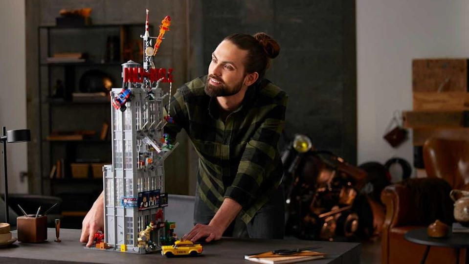 A person looks over the completed LEGO Daily Bugle set on a table