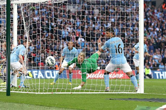 Wigan Athletic's Ben Watson (not in picture) scores the winning goal past a helpless Manchester City goalkeeper Joe Hart (centre)