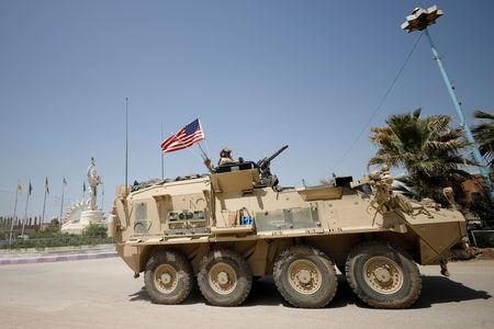 FILE PHOTO: A U.S military vehicle travels in the town of Amuda