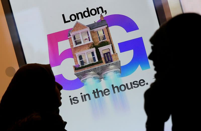 FILE PHOTO: Pedestrians walk past an advertisement promoting the 5G data network at a mobile phone store in London