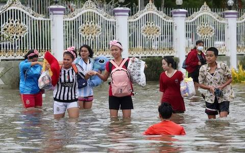 People wade through floodwaters from Tropical Storm Pabuk, Friday, Jan. 4, 2019, in Pak Phanang, in the southern province of Nakhon Si Thammarat - Credit: Thanis Sudto/AP