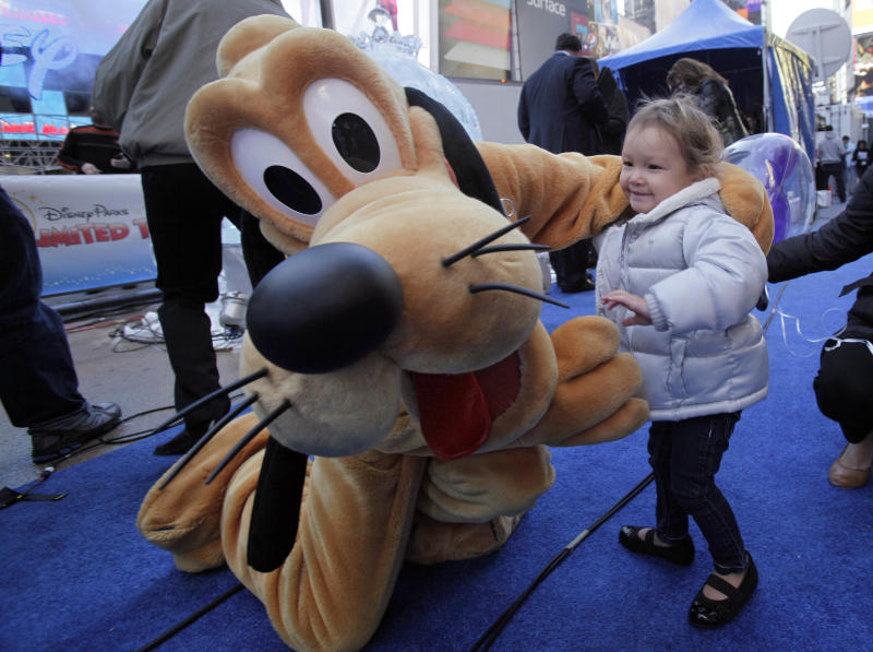 """Two-year-old Adisen Lee, from New York, meets Disney character Pluto in New York's Times Square, Wednesday, Oct. 17, 2012. On Wednesday, Disney announced a new program for 2013, """"Limited Time Magic,"""" in which guests will encounter surprise weekly themes at Disney parks in Florida and California. The program was described as """"52 weeks of magical experiences big and small that appear, then disappear as the next special surprise debuts."""" For example, a weeklong Valentine's Day celebration might include pink lighting on Disney castles, surprise meet-and-greets with Disney characters and candlelit dinners for lovebirds. (AP Photo/Richard Drew)"""