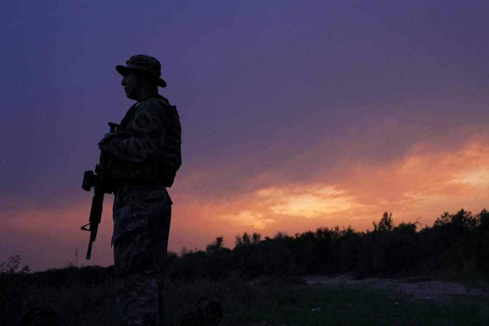 A member of the Texas Military Department stands guard along the U.S.-Mexico border Tuesday, May 11, 2021, in Roma, Texas. The U.S. government continues to report large numbers of migrants crossing the U.S.-Mexico border with an increase in adult crossers. But families and unaccompanied children are still arriving in dramatic numbers despite the weather changing in the Rio Grande Valley registering hotter days and nights. (AP Photo/Gregory Bull)