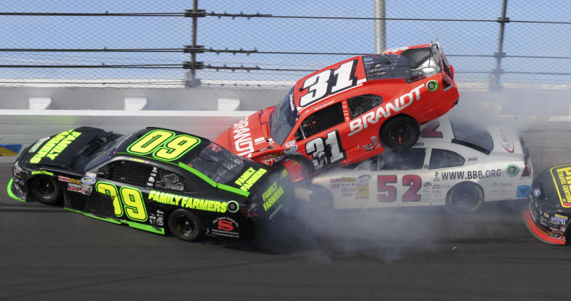 Justin Allgaier (31) rides on top of Reed Sorenson (52) as Kenny Wallace (09) hits the wall during the NASCAR Drive4COPD 300 Nationwide series auto race in Daytona Beach, Fla., Saturday, Feb. 25, 2012. (AP Photo/Zack Hughes)
