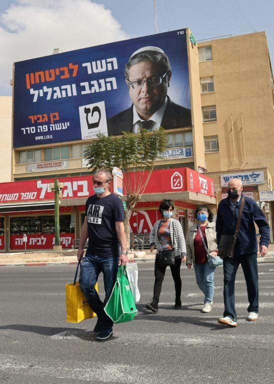 Israelis pass a campaign poster for Ben-Gvir in the city of Beersheba this week