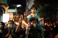 A pro-democracy protester and a child on their shoulders holds up the three-finger salute during a demonstration in Bangkok on October 15, 2020, after Thailand issued an emergency decree following an anti-government rally the previous day. (Photo by Jack TAYLOR / AFP) (Photo by JACK TAYLOR/AFP via Getty Images)