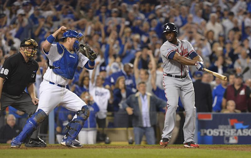 Los Angeles Dodgers catcher A.J. Ellis celebrates as Atlanta Braves' Justin Upton, right, strikes out on a foul tip in the ninth inning for the final out of Game 4 of the National League baseball division series Monday, Oct. 7, 2013, in Los Angeles. The Dodgers won 4-3, and advanced to the NL championship series. (AP Photo/Mark J. Terrill)