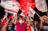 Supporters of right-wing Turkish nationalist Ersin Tatar celebrate his win in the presidential election in the northern part of Nicosia on Sunday night