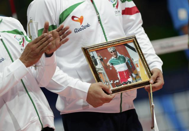 2016 Rio Paralympics - Sitting Volleyball - Final - Men's Gold Medal Match - Riocentro Pavilion 6 - Rio de Janeiro, Brazil - 18/09/2016. Members of team Iran hold a photograph of Iranian cyclist Sarafraz Bahman Golbarnezhad, REUTERS/Ueslei Marcelino FOR EDITORIAL USE ONLY. NOT FOR SALE FOR MARKETING OR ADVERTISING CAMPAIGNS.