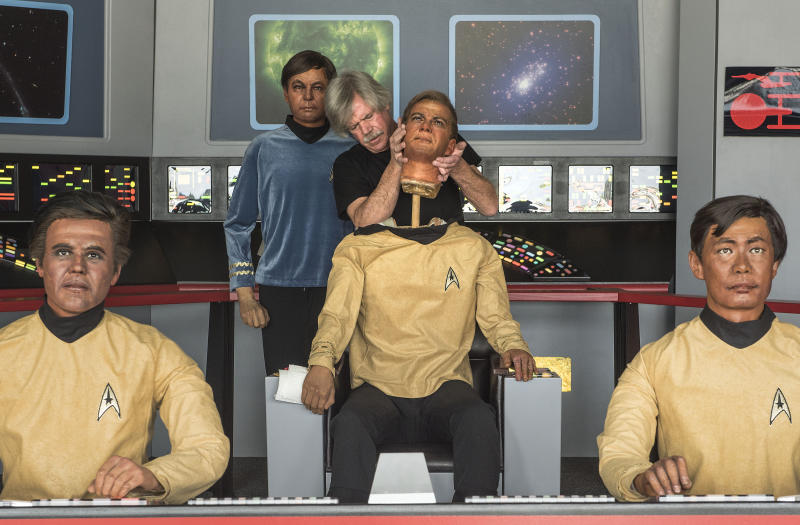 In this Saturday, March 25, 2017 photo, Steve Greenthal puts on the head of his Captain Kirk wax figure at the Fullerton Airport before donating them to the Hollywood Science Fiction Museum in Fullerton, Calif. The figures were purchased when the Movieland Wax Museum in Buena Park went out of business. The figures are being restored for a five-year tour to raise money to get the museum a permanent home. (Nick Agro/The Orange County Register via AP)