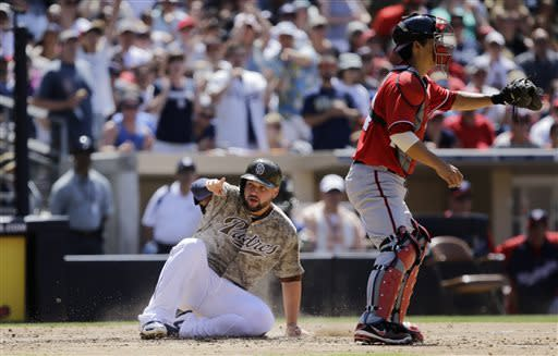 San Diego Padres' Yonder Alonso slides in safely as Washington Nationals catcher Kurt Suzuki takes in a late throw during the fifth inning of a baseball game in San Diego, Sunday, May 19, 2013. Alonso scored a base hit by Jedd Gyorko, his second rbi of the game. (AP Photo/Lenny Ignelzi)