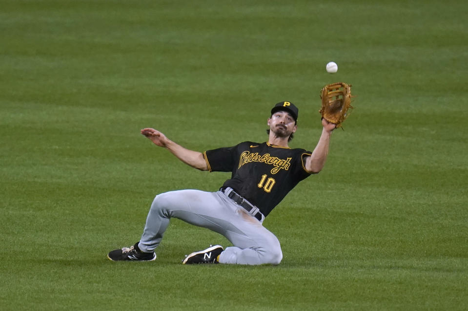 Pittsburgh Pirates center fielder Bryan Reynolds slides to catch a fly ball by St. Louis Cardinals' Harrison Bader for an out during the seventh inning of a baseball game Tuesday, May 18, 2021, in St. Louis. (AP Photo/Jeff Roberson)
