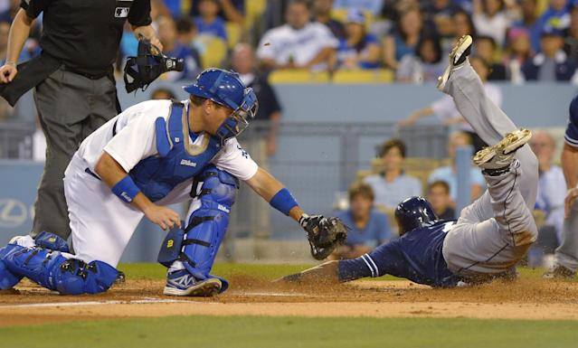 San Diego Padres' Rymer Liriano, right, scores under the tag of Los Angeles Dodgers catcher A.J. Ellis on a single by Eric Stults and a fielding error by Scott Van Slyke during the second inning of a baseball game, Wednesday, Aug. 20, 2014, in Los Angeles. (AP Photo/Mark J. Terrill)