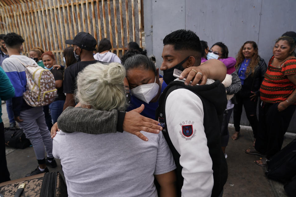 FILE - In this July 5, 2021, file photo, Alex Cortillo, right, of Honduras gets a hug from Erika Valladares Ponce, of Honduras, center, and others, as he waits to cross into the United States to begin the asylum process in Tijuana, Mexico. Two nongovernmental organizations said Friday, July 30, 2021, that they are ending cooperation with the Biden Administration to identify the most vulnerable migrants waiting in Mexico to be admitted to the United States to seek asylum. (AP Photo/Gregory Bull, File)