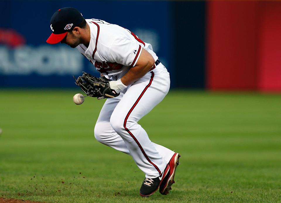 Dan Uggla #26 of the Atlanta Braves bobbles a groundball hit by David Freese #23 of the St. Louis Cardinals in the seventh inning during the National League Wild Card playoff game at Turner Field on October 5, 2012 in Atlanta, Georgia. (Photo by Kevin C. Cox/Getty Images)