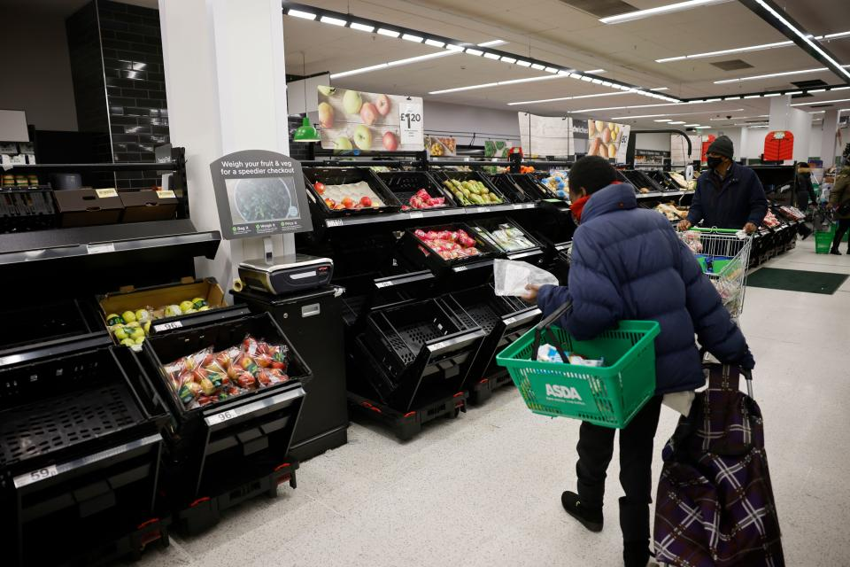 Shoppers wearing a face mask or covering due to the COVID-19 pandemic, look at empty fruit and vegetable troughs inside an ASDA supermarket in Walthamstow in north east London on December 22, 2020. - The British government said Tuesday it was considering tests for truckers as part of talks with French authorities to allow the resumption of freight traffic suspended due to a new strain of coronavirus. Britain was plunged into fresh crisis last week with the emergence of a fresh strain of the virus, which is believed to be up to 70 percent more transmissible than other forms. (Photo by Tolga Akmen / AFP) (Photo by TOLGA AKMEN/AFP via Getty Images)