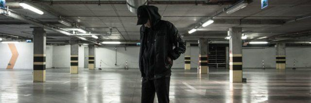 photo of young man standing in car parking garage at night alone