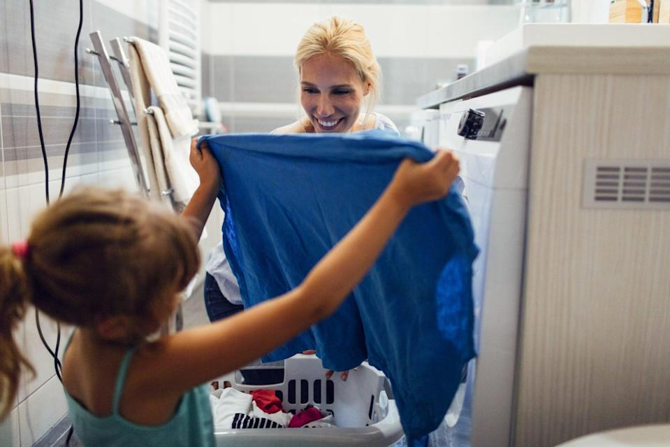 An image of a mother and daughter doing laundry.