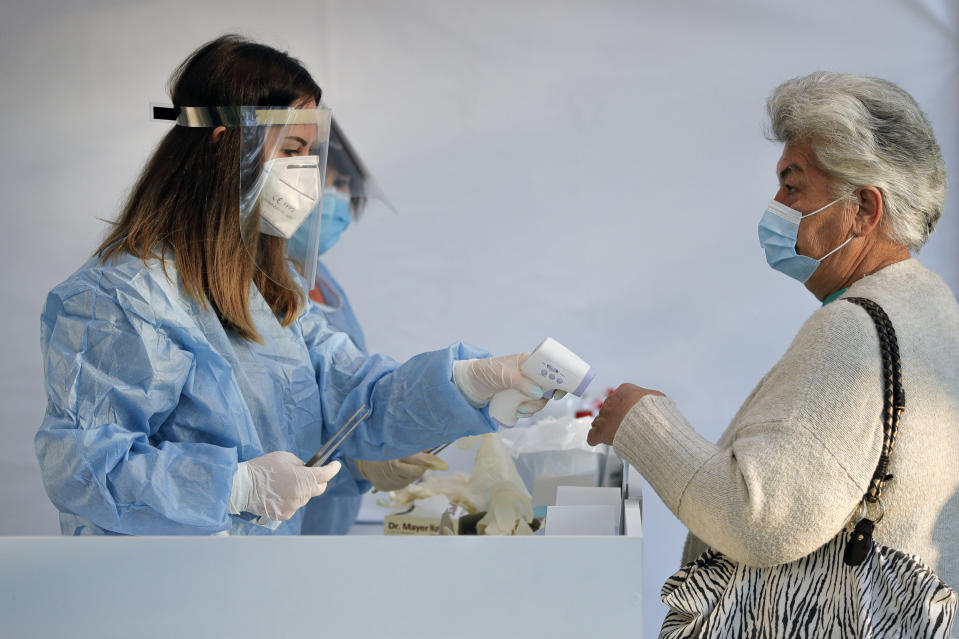 An electoral staff member checks the temperature of a woman, wearing a face mask for protection against the COVID-19 infection, before allowing her in a voting station in Bucharest, Romania, Sunday, Sept. 27, 2020. Some 19 million registered voters are choosing local officials, council presidents and mayors to fill more than 43,000 positions across the European Union nation. ( AP Photo/Vadim Ghirda)