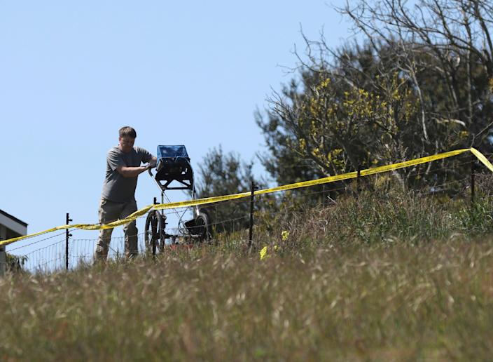 In this March 16, 2021, file photo, an investigator uses ground penetrating radar to search the backyard of the home of Ruben Flores, in Arroyo Grande, Calif. Flores is the father of Paul Flores, who remains the prime suspect in the disappearance of Kristin Smart in 1996.