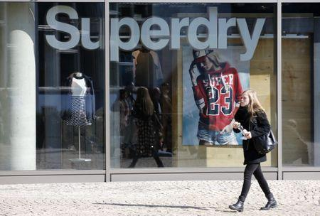FILE PHOTO: A woman walks past a Superdry fashion store in Berlin, Germany, March 17, 2016.   REUTERS/Fabrizio Bensch