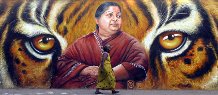 A woman walks in front of a portrait of Jayalalithaa, a former film actress and now head of the state opposition party, the All India Anna Dravida Munnetra Kazhagam (AIADMK), in the southern Indian city of Chennai March 2, 2009. India will hold a general election between April 16 and May 13, election officials said on Monday, kicking off a mammoth process in which 714 million people will be able to cast their votes. REUTERS/Babu (INDIA)