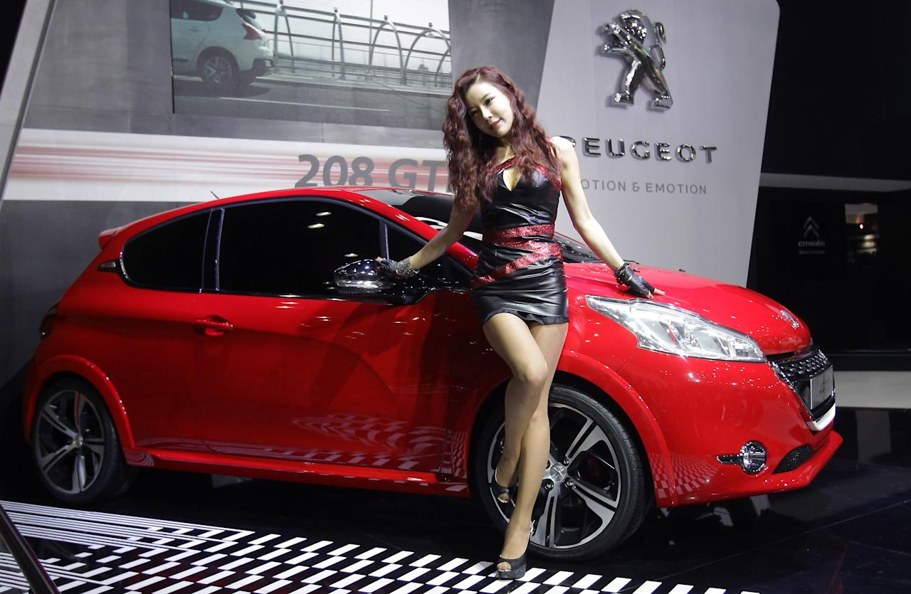 GOYANG, SOUTH KOREA - MARCH 28:  A Model poses next to a PEUGEOT 208 GTi at the Seoul Motor Show 2013 on March 28, 2013 in Goyang, South Korea. The Seoul Motor Show 2013 will be held in March 29-April 7, featuring state-of-the-art technologies and concept cars from global automakers. The show is its ninth since the first one was held in 1995. About 384 companies from 14 countries, including auto parts manufacturers and tire makers, will set up booths to showcase trends in their respective industries, and to promote their latest products during the show.  (Photo by Chung Sung-Jun/Getty Images)