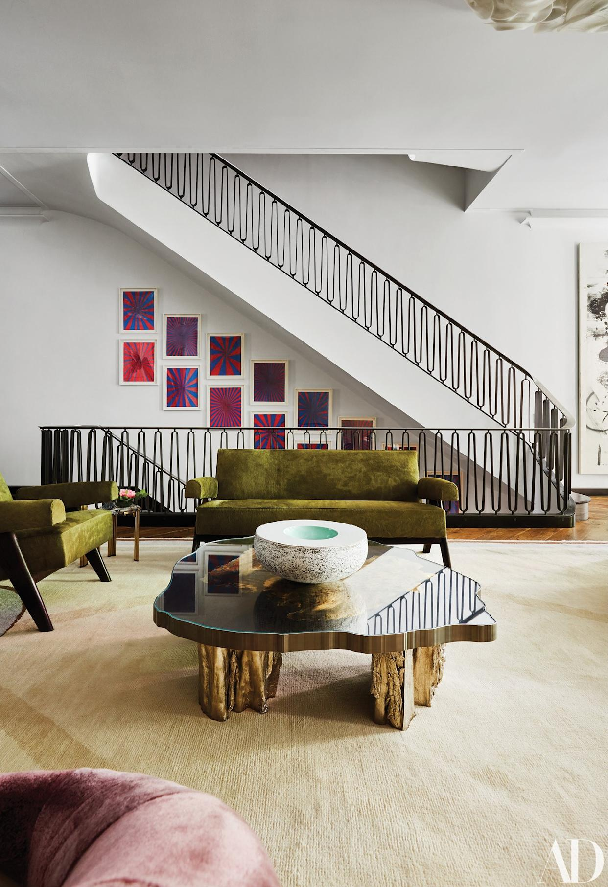 """<div class=""""caption""""> In the living room, a settee and a pair of chairs by Pierre Jeanneret surround a cocktail table by Maria Pergay. Artwork by Mark Grotjahn lines the staircase. </div>"""