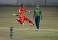 Zimbabwe's batsman Sikandar Raza, in red, jumps to celebrate after playing the winning shot in super over during the 3rd one-day international cricket match against Pakistan at the Pindi Cricket Stadium, in Rawalpindi, Pakistan, Tuesday, Nov. 3, 2020. (AP Photo/Anjum Naveed)