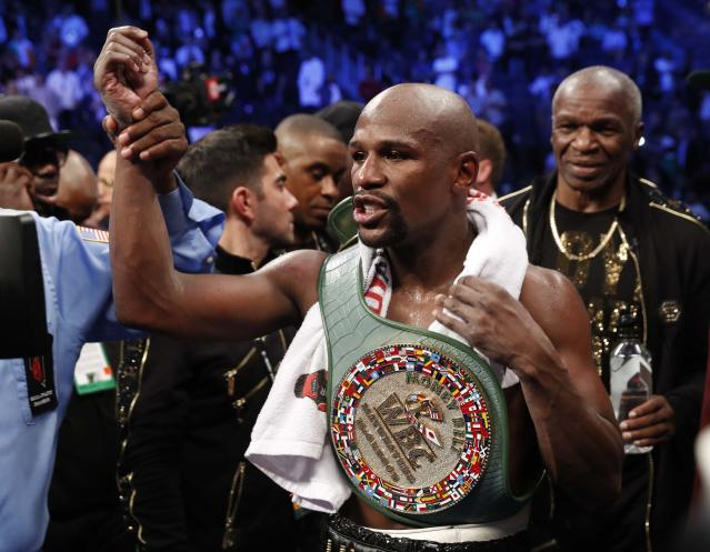 Floyd Mayweather Jr. celebrates with the belt after winning the fight (REUTERS/Steve Marcus)