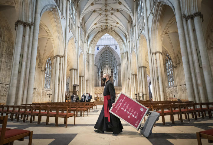 The Reverend Michael Smith moves a Covid information board in York Minster, in York, England, Monday May 17, 2021, as indoor hospitality and entertainment venues reopen to the public following the further easing of lockdown restrictions in England. (Danny Lawson/PA via AP)