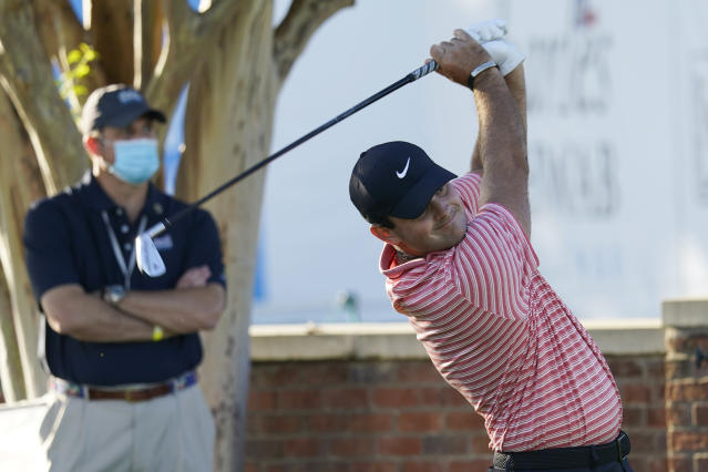 Coby Wooten, left, watches as Patrick Reed tees off at the 10th hole during the first round of the Charles Schwab Challenge golf tournament at the Colonial Country Club in Fort Worth, Texas, Thursday, June 11, 2020. (AP Photo/David J. Phillip)