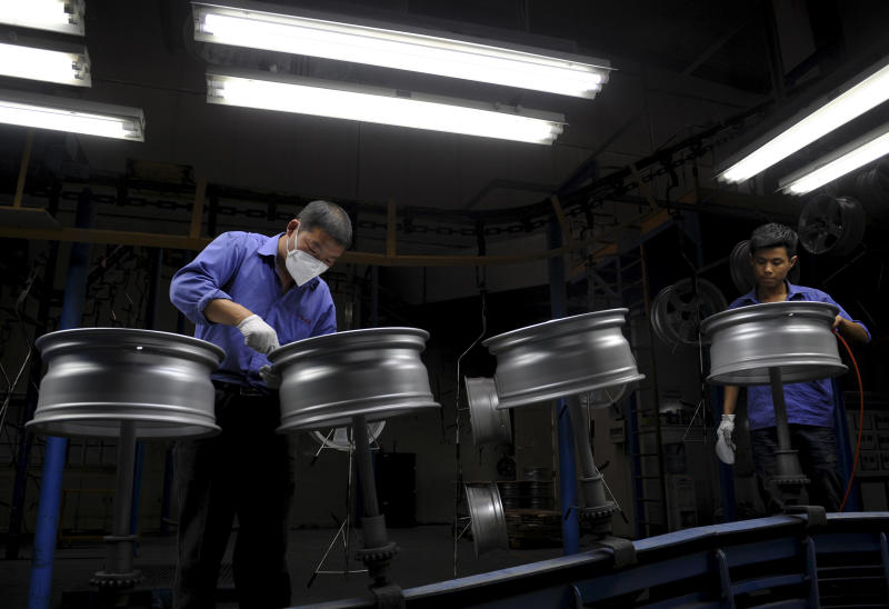 Workers labor at a factory making automobile wheels in Shaoxing city in east China's Zhejiang province on Monday April, 15, 2013. China's economic growth slowed unexpectedly in the first three months of the year, fueling concern about the strength of its shaky recovery. (AP Photo) CHINA OUT
