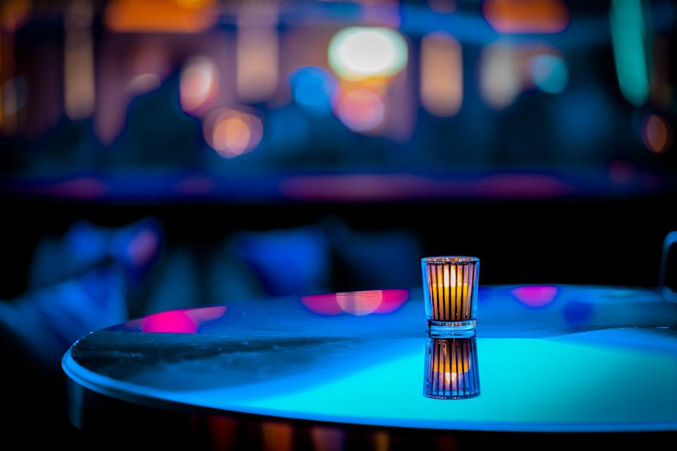 Minimalistic or abstract candle on table at a nightclub with out of focus background -- teal, blue and pink bokeh