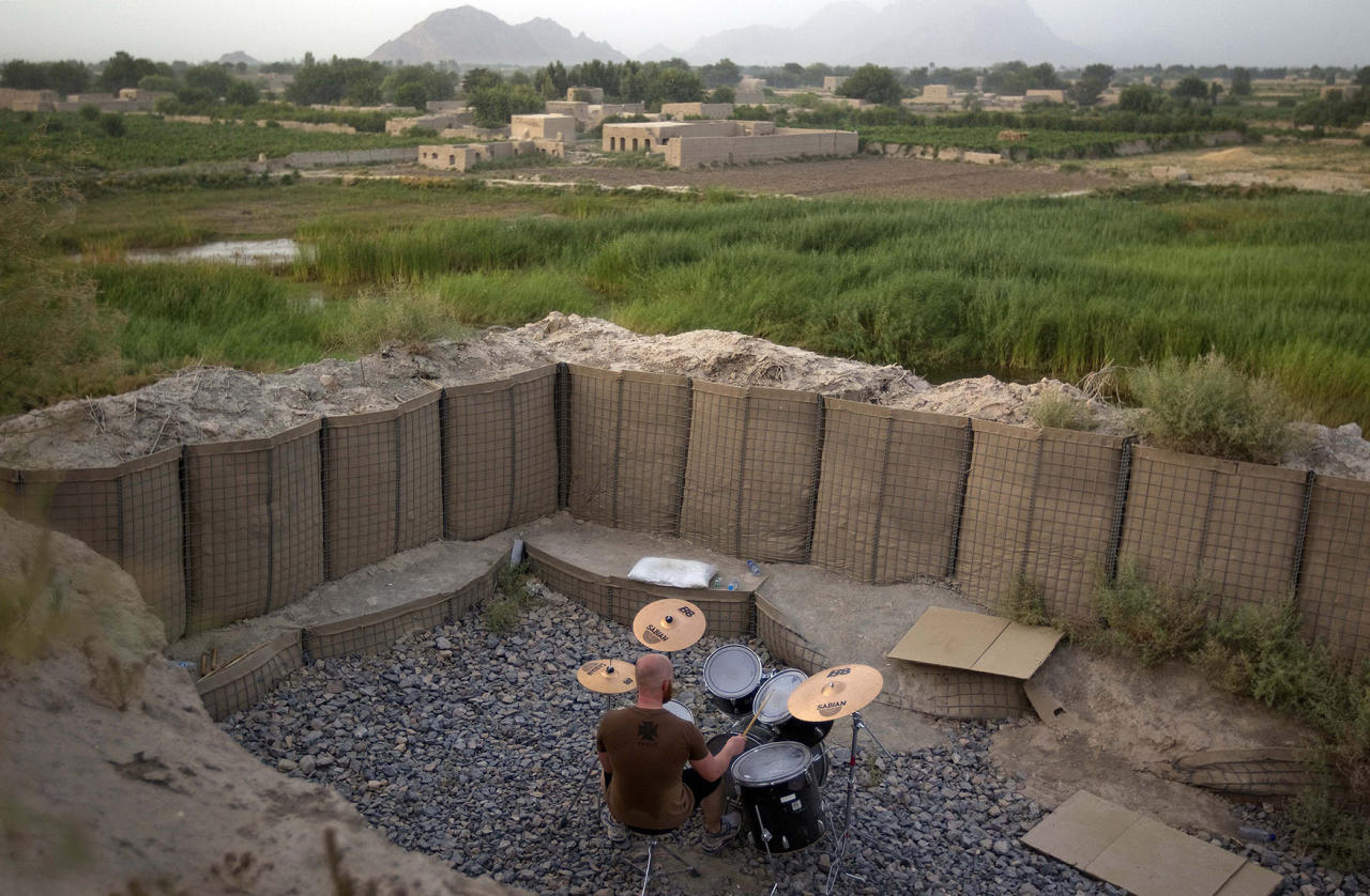 <p>Canadian Forces soldier, Cpl. Ben Vandandaigue, plays on a drum kit, June 24, 2011, on Forward Operating Base Sperwan Ghar overlooking the Panjwaii district of Kandahar province, Afghanistan. (AP Photo/David Goldman) </p>