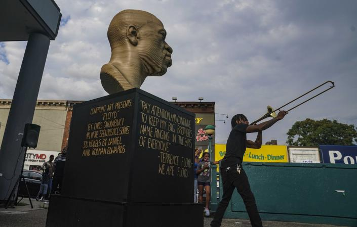 """Jonte """"Jonoel"""" Lancaster plays trombone during a celebration for the refurbished George Floyd statue, after it was vandalized following its Juneteenth installation, Thursday, July 22, 2021, in the Flatbush section of Brooklyn borough of New York. (AP Photo/Bebeto Matthews)"""