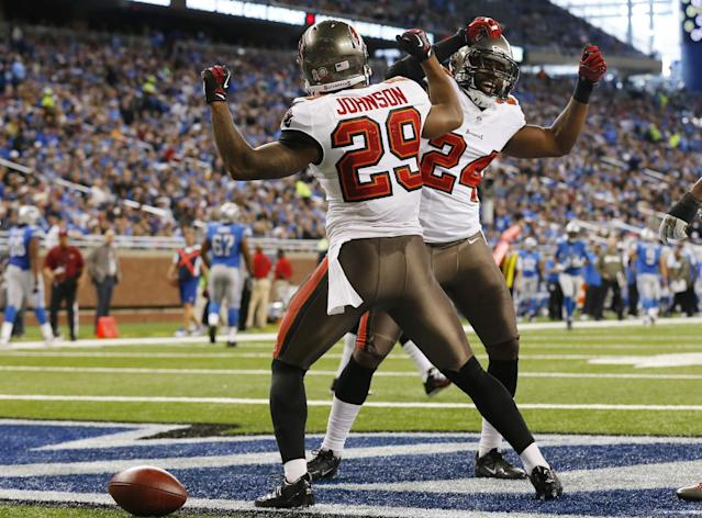 Tampa Bay Buccaneers cornerback Leonard Johnson (29) celebrates his 48-yard interception for a touchdown with teammate Darrelle Revis during the first half of an NFL football game against the Detroit Lions at Ford Field in Detroit, Sunday, Nov. 24, 2013. (AP Photo/Paul Sancya)