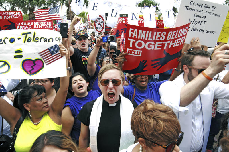 """FILE - In this June 28, 2018 file photo, protesters chant """"Families belong together!"""" as they walk to the front doors of the federal courthouse in Brownsville, Texas, to bring attention to the U.S. immigration policy. A federal judge, responding to a plan to reunify children separated at the border, said he was having second thoughts about his belief that the Trump administration was acting in good faith to comply with his orders. The Justice Department on Friday, July 13 filed a plan to reunify more than 2,500 children 5 years old and older by a court-imposed deadline of July 26 using """"truncated"""" procedures to verify parentage and perform background checks that excludes DNA testing and other steps it took to reunify children under 5. The administration said the abbreviated vetting puts children at significant safety risk but is needed to meet the deadline.  (Miguel Roberts/The Brownsville Herald via AP, File)"""